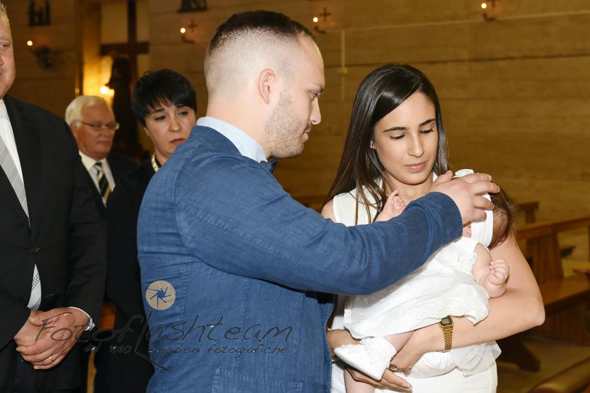 Bambino con genitori cerimonia battesimo