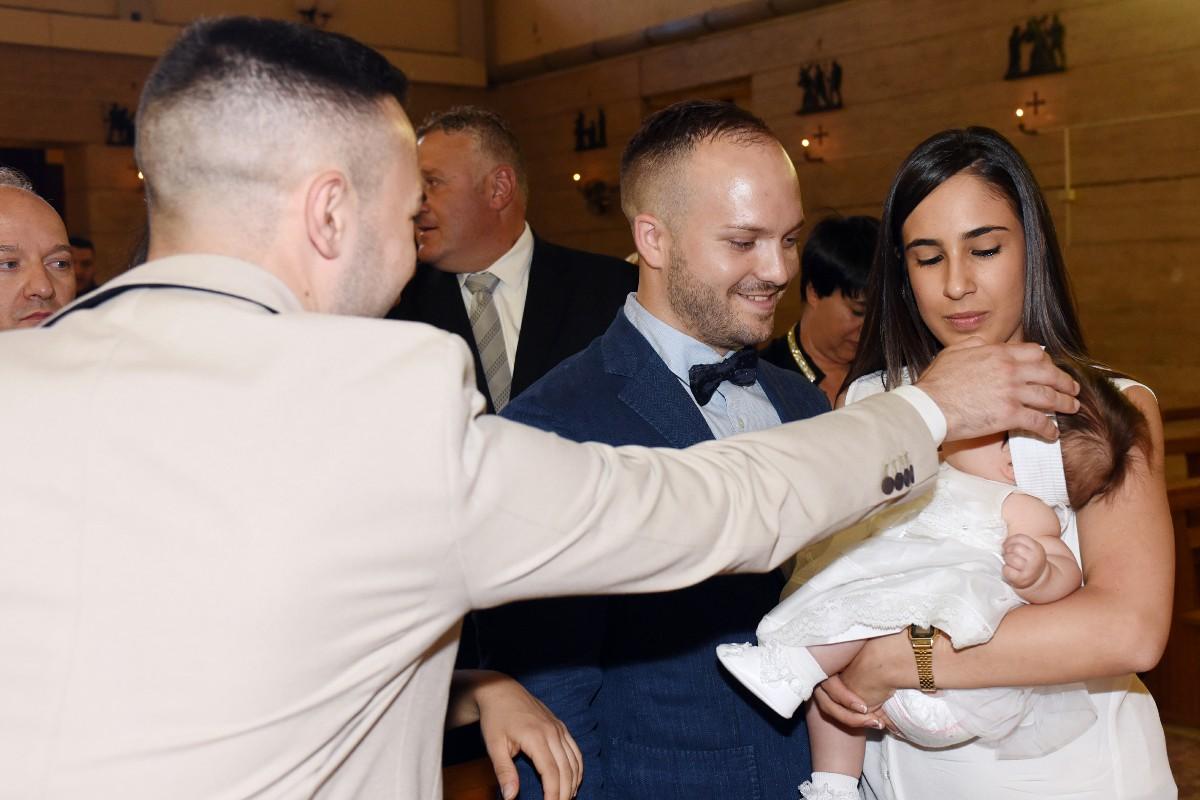 Bambino con genitori e padrino servizio foto battesimo