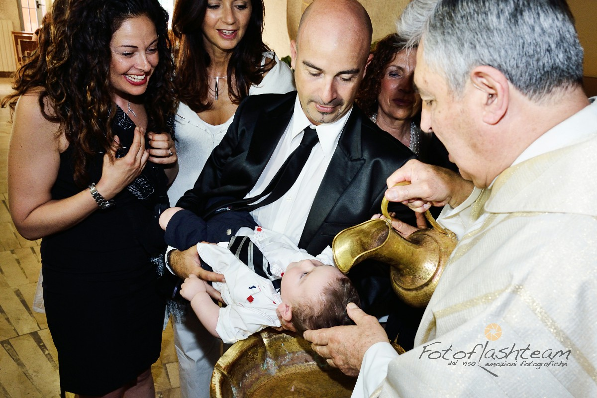 Bambino con genitori rito del battesimo acqua battezzando