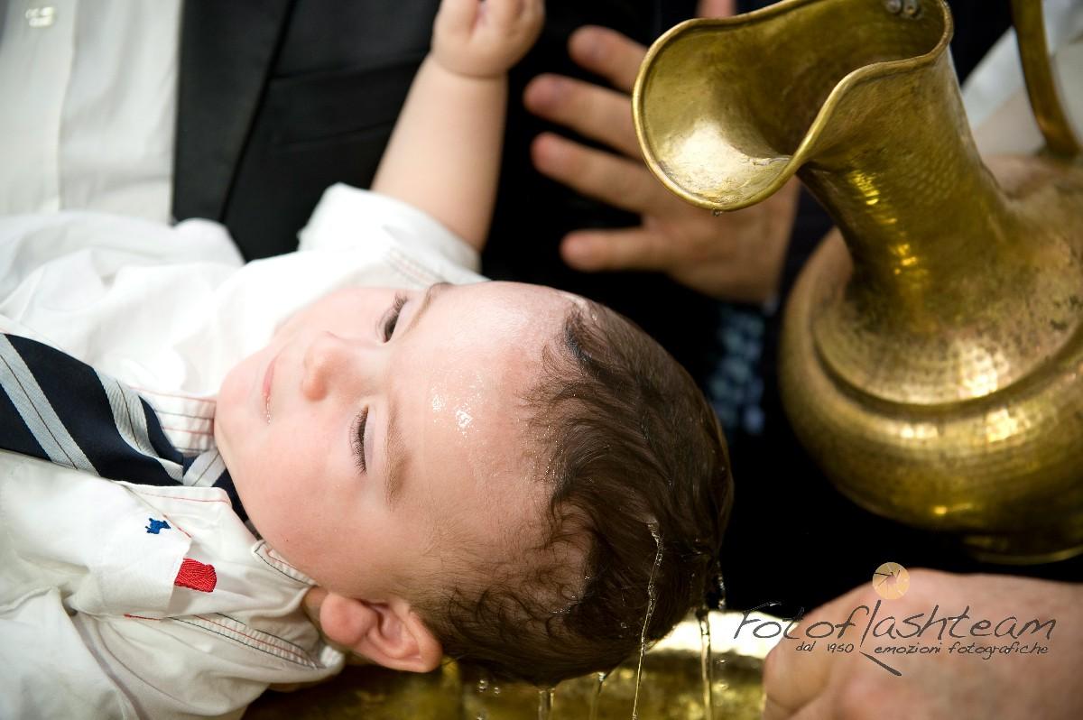 Bambino rito del battesimo acqua battezzando